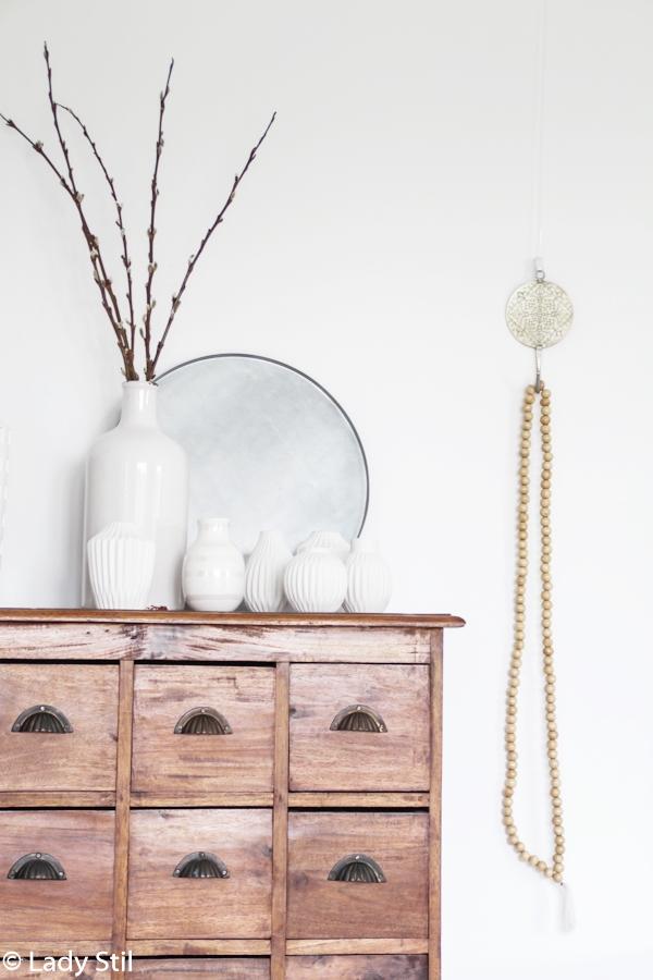 antike holzfarbene Apothekerkommode mit weißen Vasen, einer Holzkette und einem runden silbernen Tablett als Deko