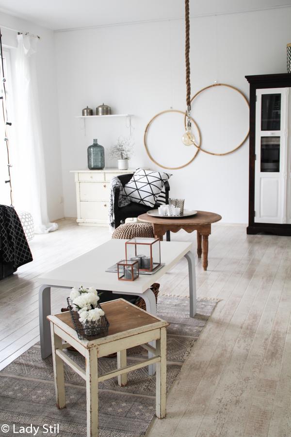Blick ins Wohnzimmer mit Wanddeko aus Hula Hoop Reifen, indischem Coffeetable, marokkanischem Schrank, marokkanischen silbernen Dosen auf einem Wandregal und diversen Dekoelementen in Kupfer, Grau und Schwarz