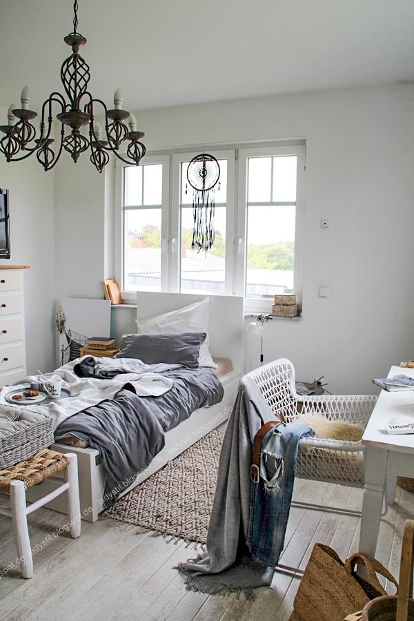Schlafzimmer mit kuscheligen Decken aus natürlichen Materialien in grau weiß schwarz