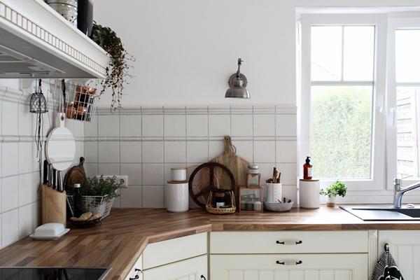 Kücheneinrichtung in Schwarz Weiß Holz mit leichten New Boho Elementen, holzfarbene Arbeitsplatte mit weißen Accessoires, House Doctor Gefäß