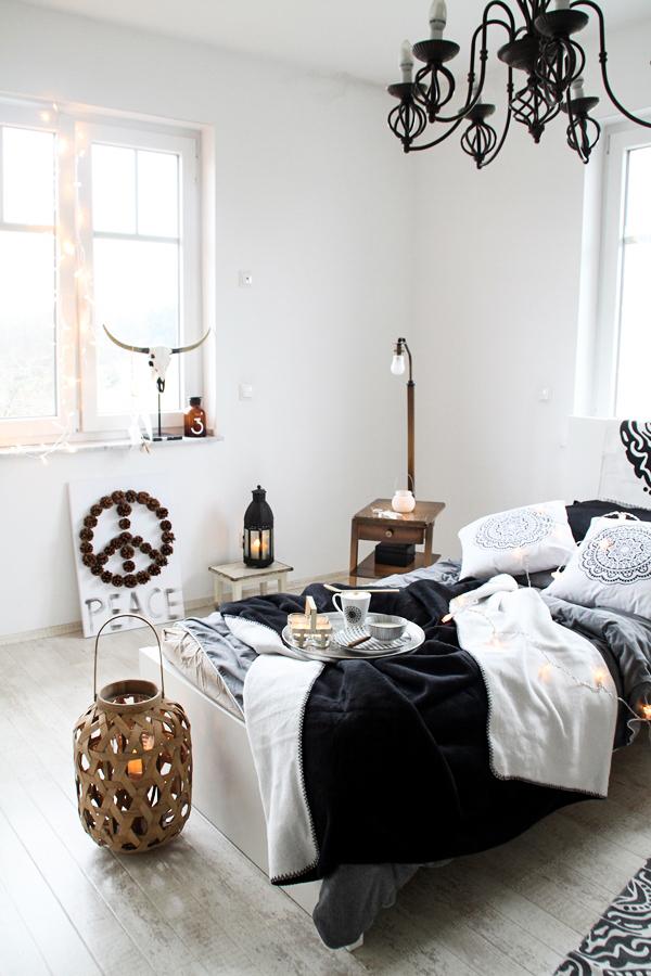 Schlafzimmerdeko im New Boho Look mit schwarz-weißen Ethnoelementen und Holz Accessoires, Bohoschädel, afrikanische Maske und Bambus-Laterne, DIY Bild mit Peacezeichen aus Tannenzapfen