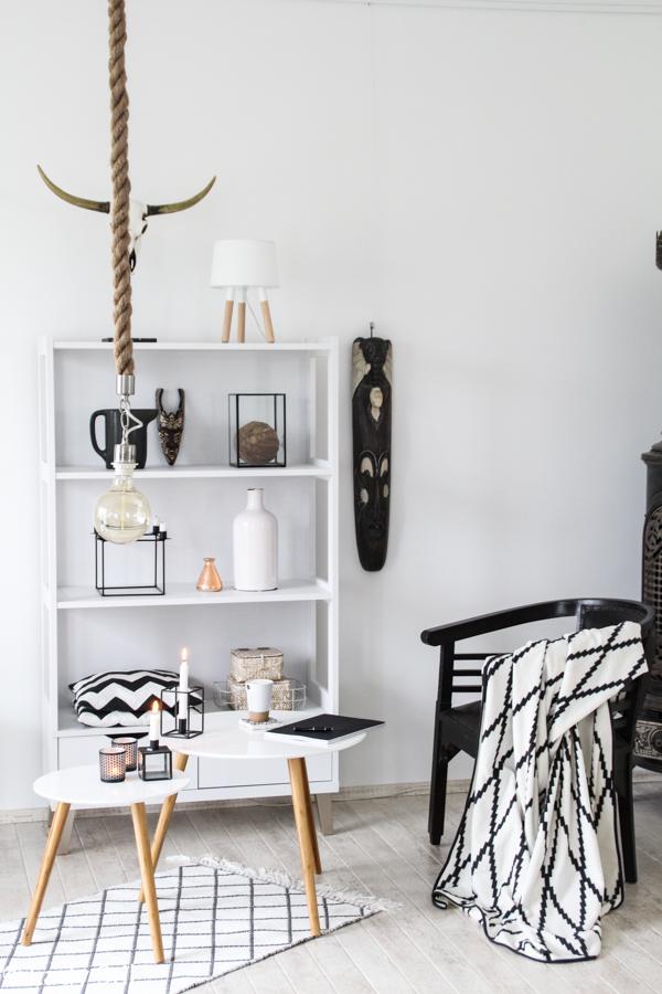 Wohnzimmer Im Scandi-Boho-Look in Weiß Schwarz Holz mit Scandi Beistelltischen von daheim.de, Bohoelemente wie Skull, Masken und Wandbehang